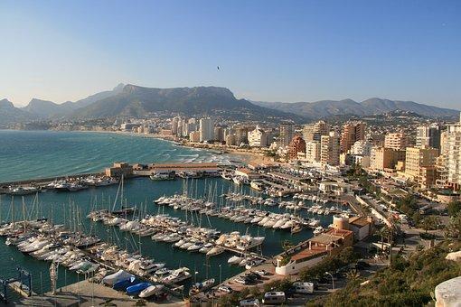 Vista de puertos con barcos, también playa y edificios, Alquiler de vehículos en Calpe VIVACARS