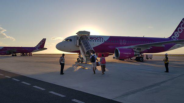 Man and woman about to board a plane in evening sunset