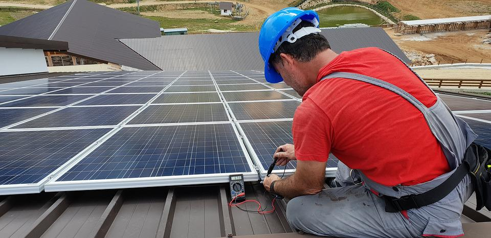 The contractor installing solar panels on the roof.