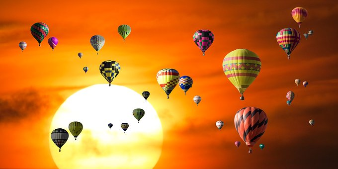 Hotair balloons floating in a bright yellow sky