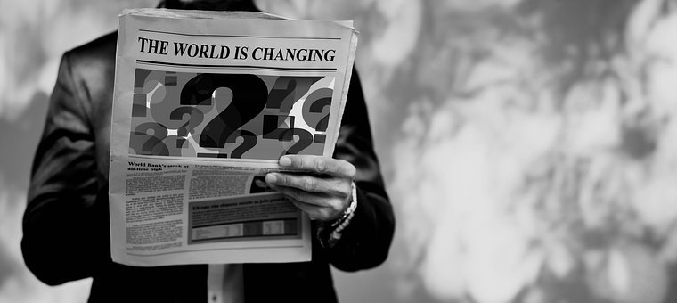 A man in suit holding a newspaper with title