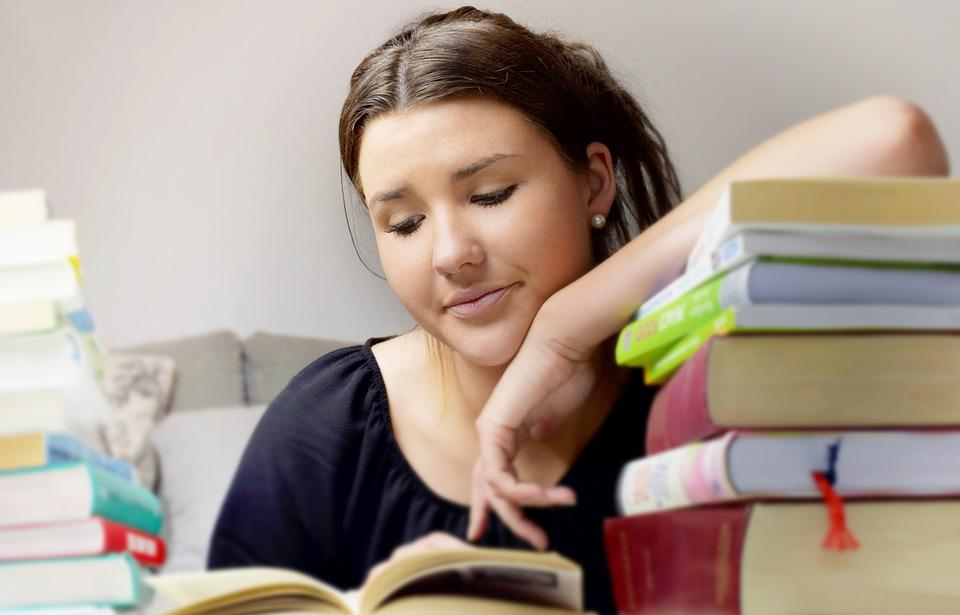 calm girl with pile of books