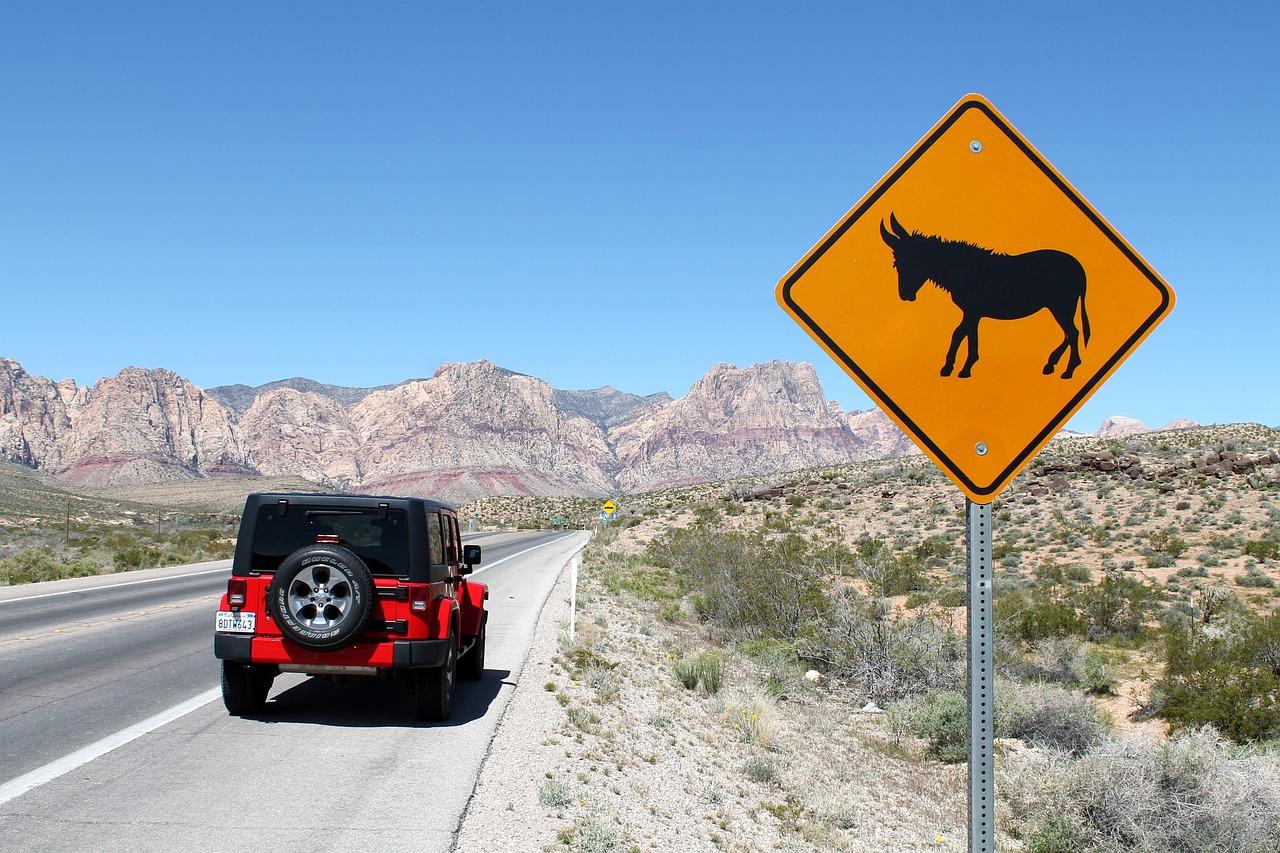 Red Jeep Wrangler on a desert road
