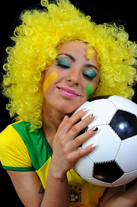 Woman holding a soccer ball in brazil colors
