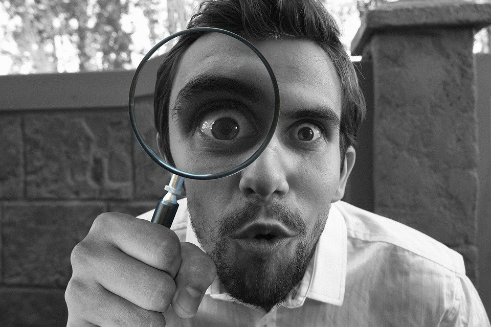 Man looking at a Magnifying Glass