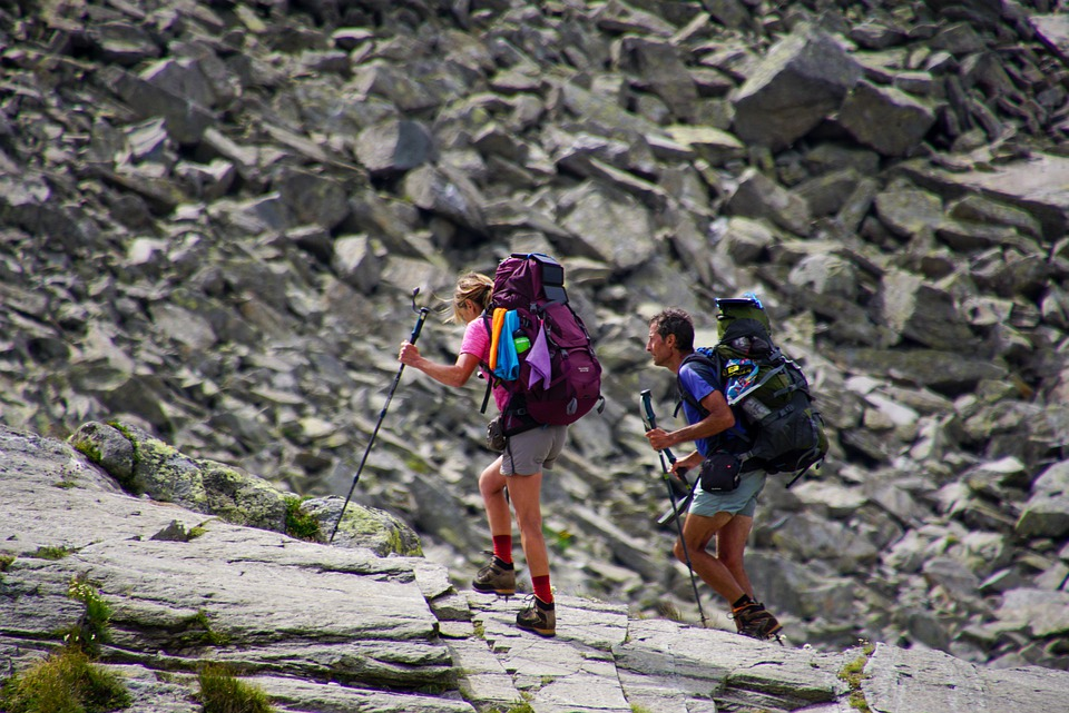 Two people hiking with large backpacks looking warm and tired