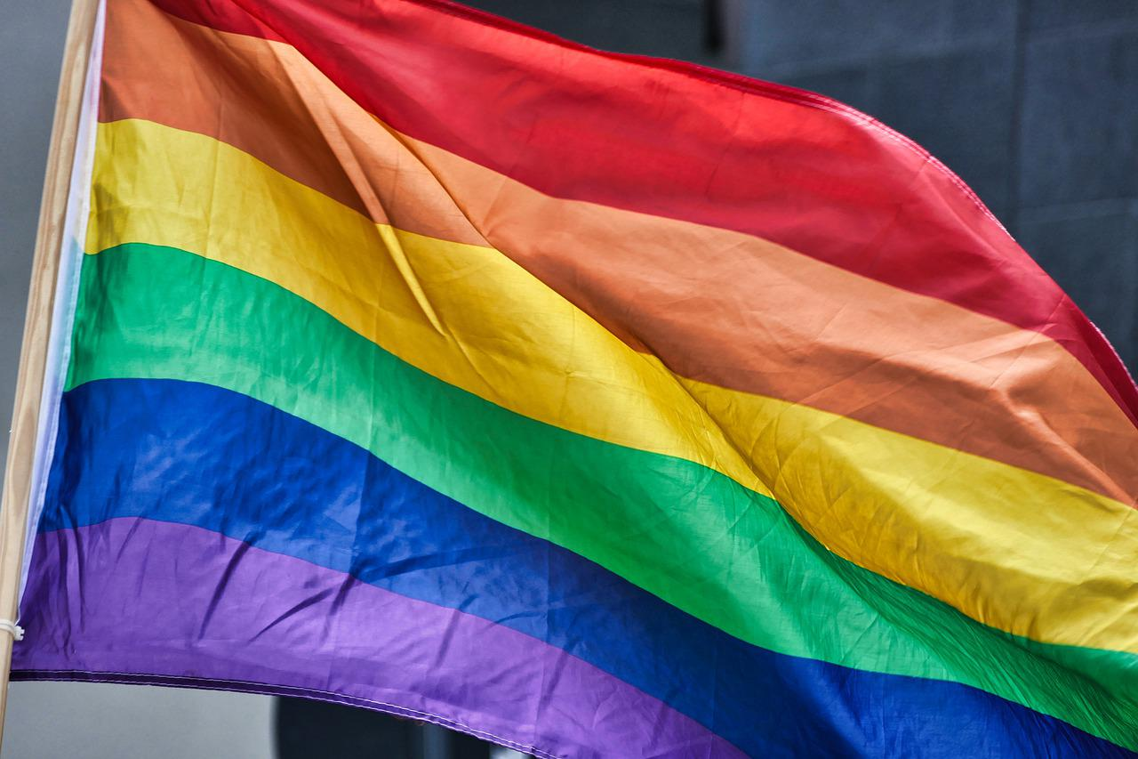 A photograph of a rainbow flag with red at top and purple at bottom, symbolizing gay pride.