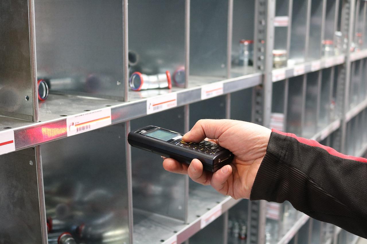 Hand mit Scanner vor einem Regal mit Einzelteilen