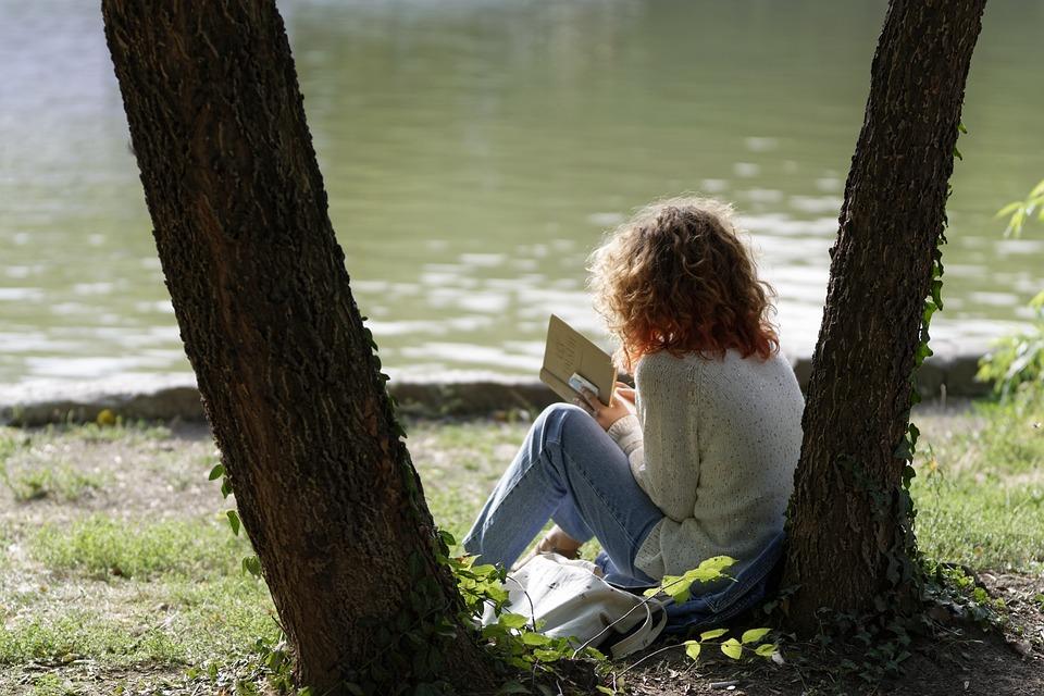 木の下で本を読む女性