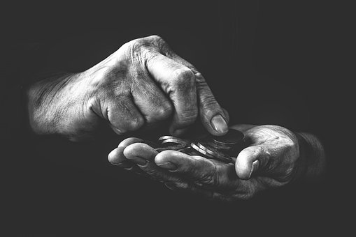 grayscale photography of human holding coins