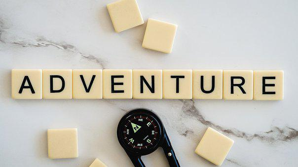 letter tiles spell out the word adventure above a compass