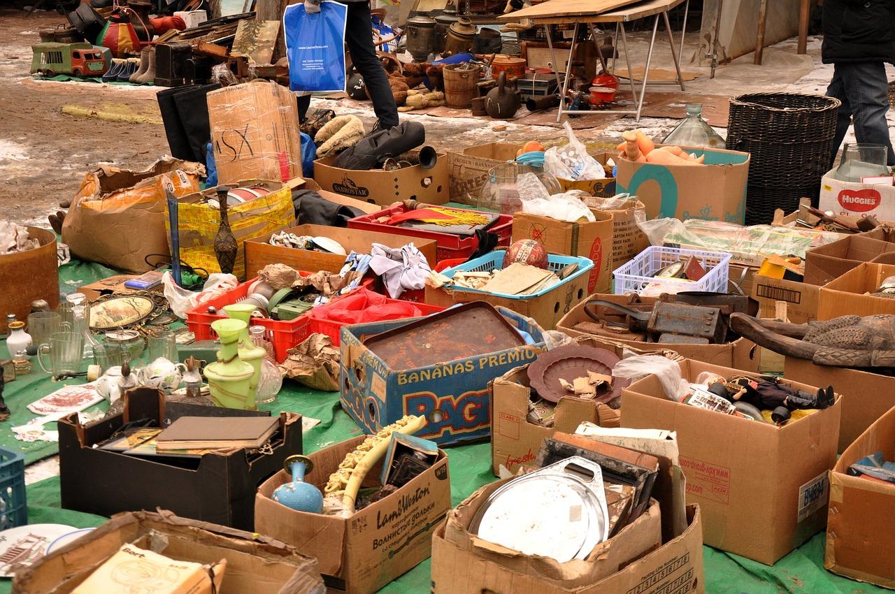Boxes of random items like home decor, kitchen items, books, etc. at a flea market