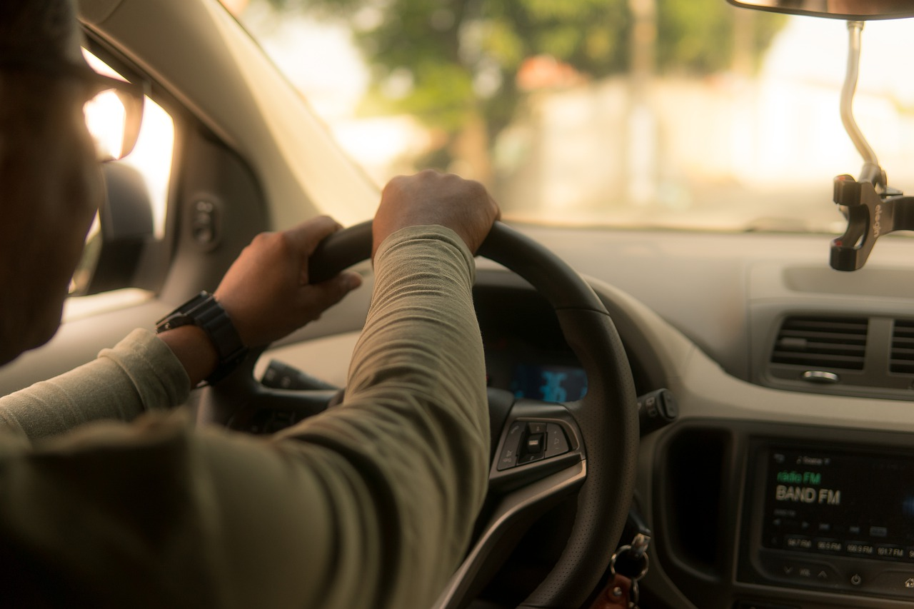 View of two hands gripping the steering wheel of a car