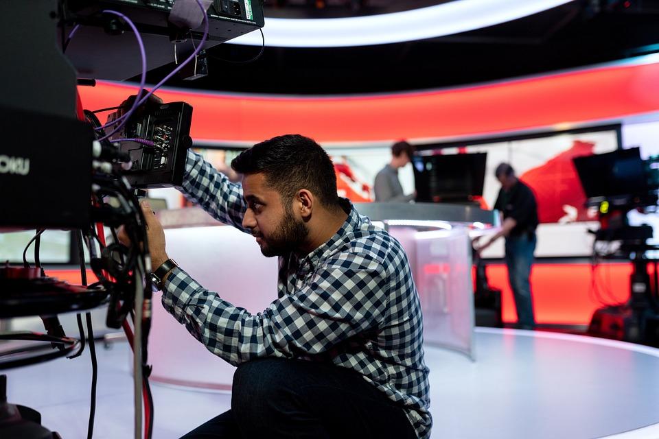 En ingeniør fikser på et kamera for pressen før en TV-sending.