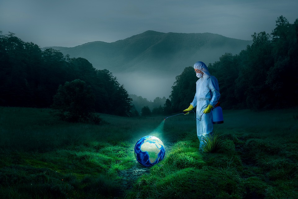 A person wearing a protective gown, gloves, mask, and goggles sprays disinfectant on a small globe of the earth.