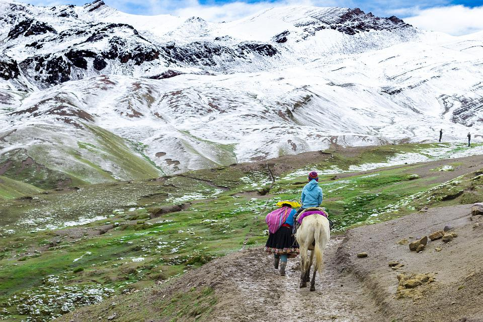 sherpa and child on a horse going up andean mountain