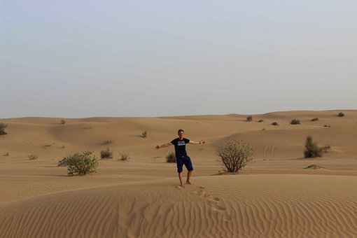 Man with soutstretched arms alone in the middle of a desert