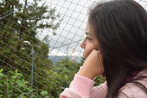 A side view of a brown-skinned girl with dark brown hair with her hand on her cheek looking disappointed