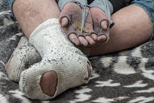 Man's legs in torn socks with arm-stretched arms for money