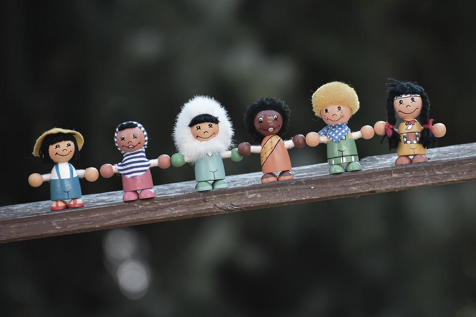 Photograph of small wooden figures representing different ethnic groups