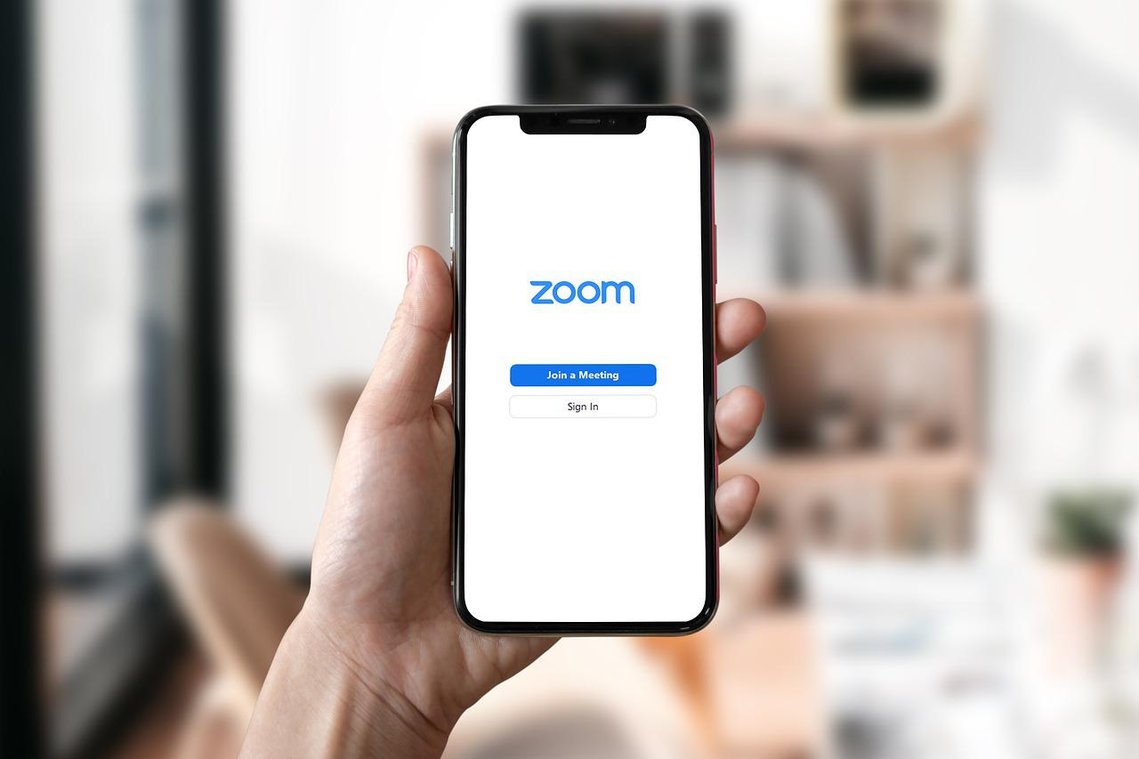 A hand holds up a mobile phone that displays a Zoom page