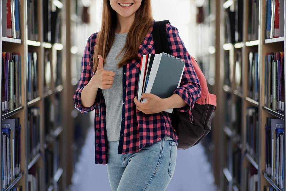 Liga Odpowiedzialnego Biznesu - rusza rekrutacja do 18. edycji - Studentka z książkami w ręku w bibliotece.